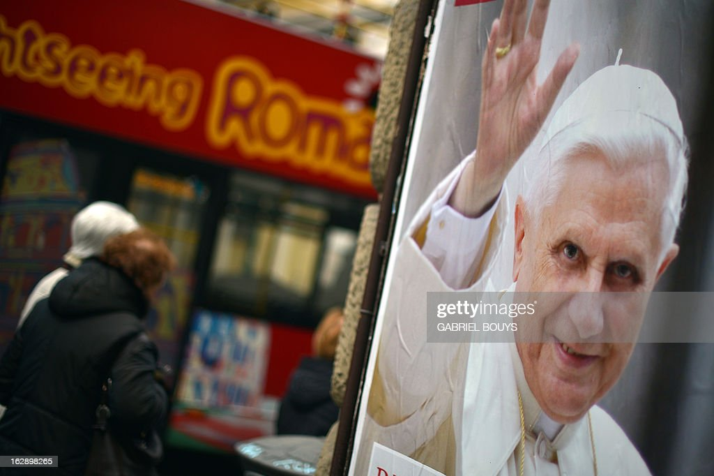 People pass by a placard of the city of Rome in homage to Pope Benedict XVI on March 1, 2013 in Rome. Pope Benedict XVI has become the day before the first pope to resign in over 700 years, telling a tearful crowd of faithful that he will now be 'a simple pilgrim' as cardinals on Friday begin preparing for a conclave in the Sistine Chapel to elect his successor.