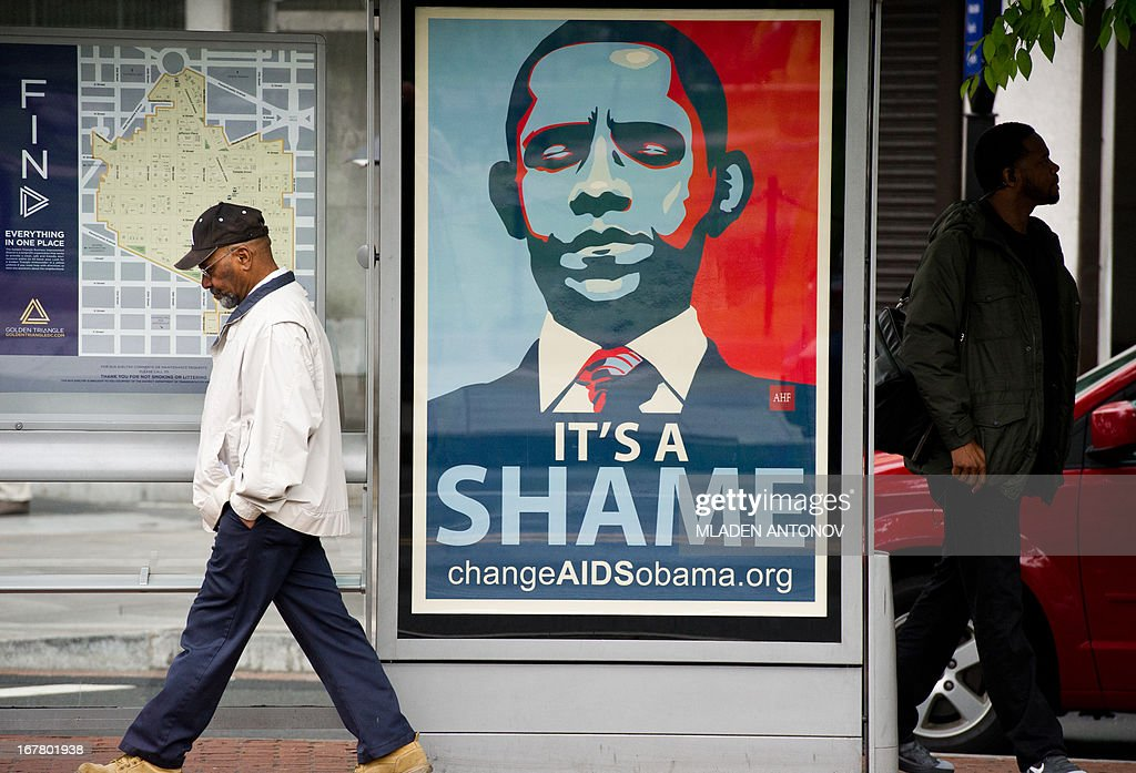 People pass by a poster depicting the US President Barack Obama and criticizing the US Government for reducing AIDS funding at a bus stop in Washington DC on April 30, 2013. An estimated 34 million people are infected with HIV worldwide, including 3.4 million children. AIDS has killed 30 million people since the beginning of the epidemic 30 years ago and an estimated 1.8 million people die from the disease each year. AFP PHOTO/ Mladen ANTONOV