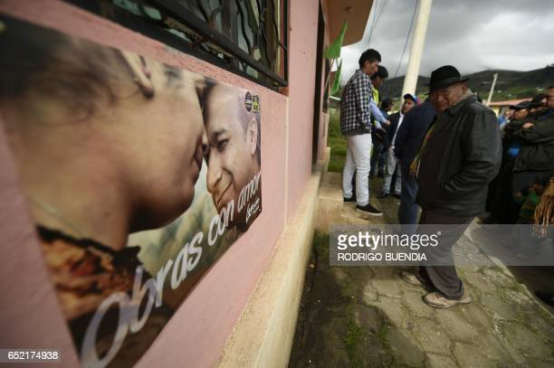 People pass by a propaganda poster of the presidential candidate of the ruling party Lenin Moreno in Zumbahua Cotopaxi province Ecuador on March 11...