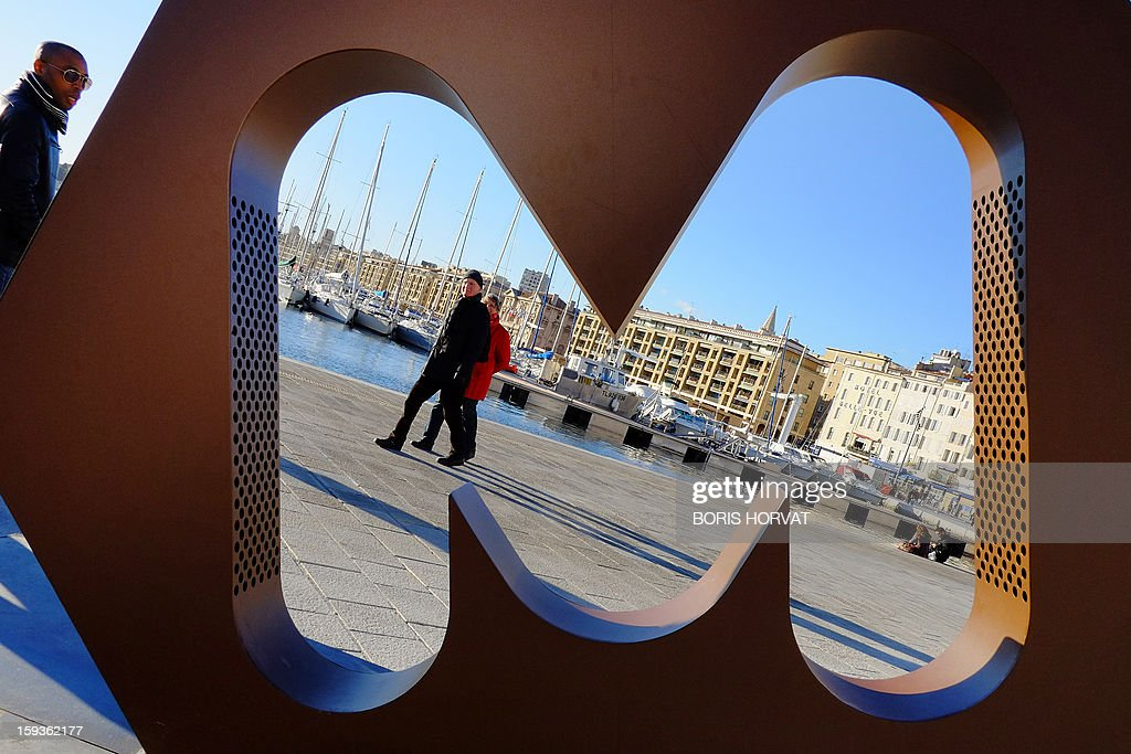 People pass by a sculpture shaped as a 'M' (for Marseille) displayed in the middle of a fountain, designed by local set designer Philippe Malta, on January 11, 2013 in Marseille, southern France, as one of a number of exhibitions opening in Marseille in relation to the city being named 2013 European 'Capital of Culture'. On January 12, the city will be named 'Capital of Culture' which will kick off a range of exhibitions and events.