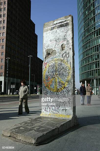 People pass by a section of the Berlin Wall at Potsdamer Platz on March 30 2005 in Berlin Germany According to a recent survey 24 percent of West...