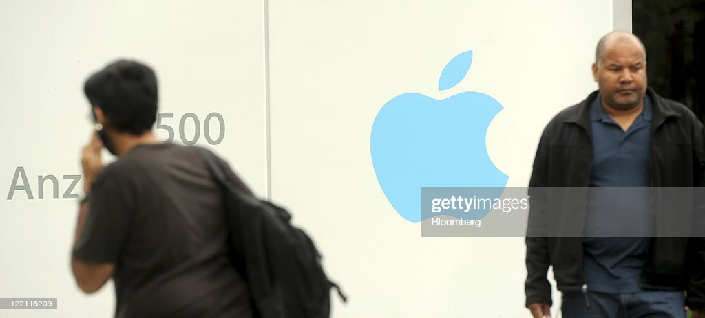 People pass by a sign at Apple Inc. headquarters in Cupertino, California, U.S., on Thursday, Aug. 25, 2011. Apple Inc. Chief Executive Officer Steve Jobs, who transformed the company he started at age 21 from a personal-computer also-ran into the world's largest technology company, resigned Wednesday. Photographer: Noah Berger/Bloomberg via Getty Images