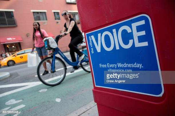 People pass by a Village Voice newspaper stand in the East Village neighborhood in Manhattan August 22 2017 The Village Voice one of the oldest and...