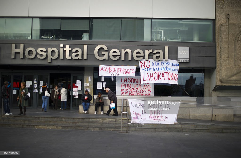 People pass by banners at the entrance of La Paz hospital on November 21, 2012 in Madrid, Spain. Doctors and nurses in the Spanish capital are preparing for a four day strike to protest against the privatisation of some parts of Spain's national health service.
