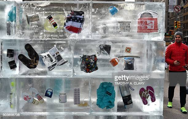 People pass by leisure items frozen in a giant block of ice during a JetBlue Airways event in Madison Square Park on January 7 2016 in New York The...