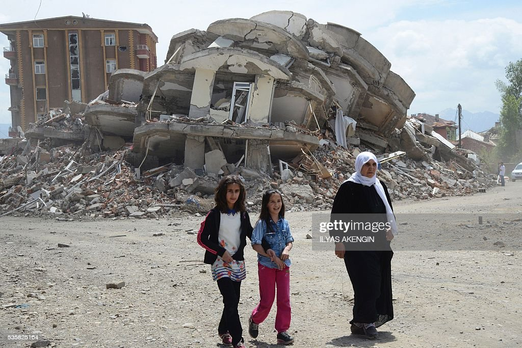 People pass by rubbles of damaged buildings following heavy fightings between Turkish government troops and Kurdish fighters after the curfew in the majority Kurdish city town of Yuksekova, southeastern Turkey near the border with Iraq and Iran, on May 30, 2016. / AFP / ILYAS
