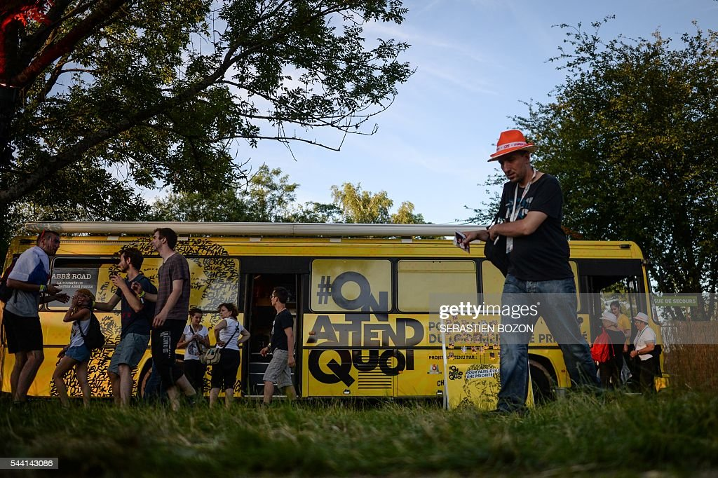 People pass by the Abbe Road bus (Abbé Pierre Fundation) during the 28th Eurockeennes music festival on July 1, 2016 in Belfort. / AFP / SEBASTIEN
