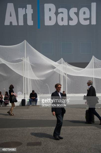 People pass by the Art Basel fair building on June 17 2014 on the preview day of the Art Basel fair that will run from June 19 to June 22 2014 in...