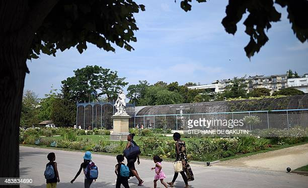 People pass by the aviary of the Jardin d'Acclimatation on August 13 2015 in the northern part of the Bois de Boulogne in Paris AFP PHOTO / STEPHANE...