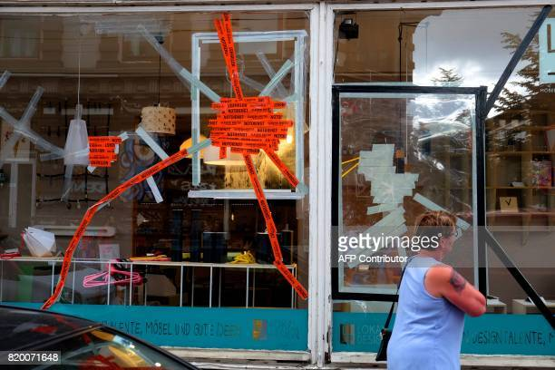 People pass by the broken window of a shop which has been damaged during the past G20 in the Schanzenviertel in Hamburg northern Germany on July 20...
