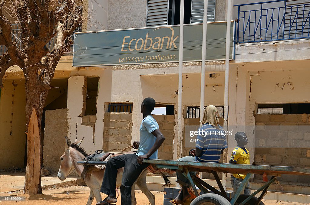 People pass by the closed entrance of an Ecobank branch, that was attacked by armed men a few months ago, in a street of Gao on July 25, 2013. The Mali presidential election on July 28 is seen as crucial to reuniting a country riven by conflict during an 18-month crisis that saw French forces intervene to push out Islamist rebels from the north.