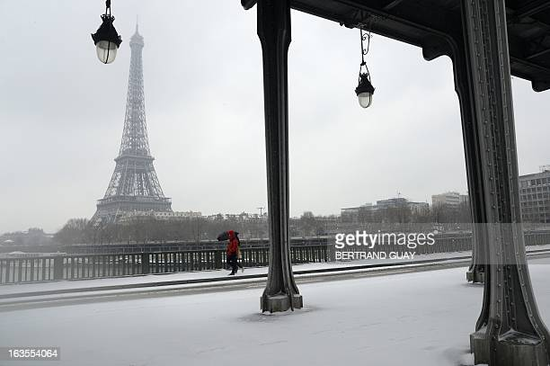 People pass by the Eiffel tower on March 12 2013 in Paris during a heavy snow storm on France More than 68000 homes were without electricity in...