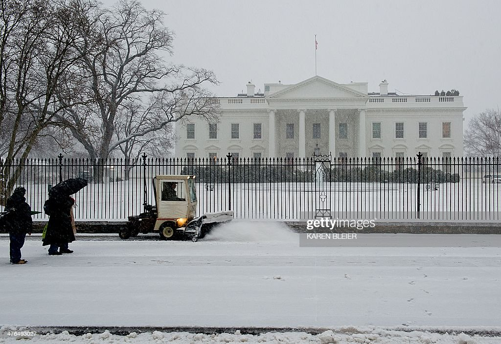 People pass by the White House during a snow storm March 3, 2014 in Washington, DC. Snow began falling in the nation's capital early Monday, and officials warned people to stay off treacherous, icy roads a scene that has become familiar to residents in the Midwest, East and even Deep South this year. Schools were canceled, bus service was halted in places and federal government workers in the DC area were told to stay home Monday. AFP PHOTO / Karen BLEIER