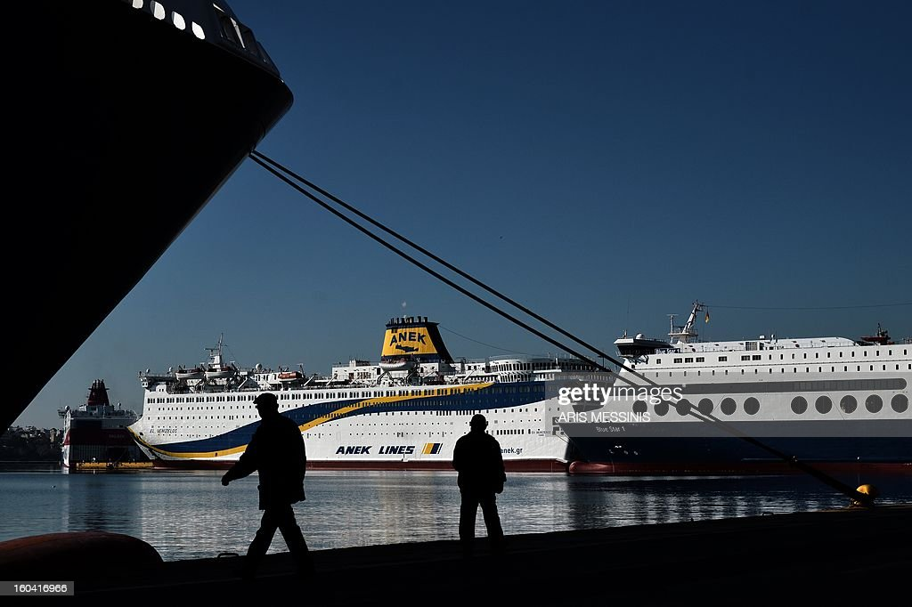 People pass docked ferries at the port of Piraeus, near Athens, during a 48-hours strike on January 31 , 2013. Sailors kicked off a two-day walkout, buses and trains were at a standstill and civil servants planned to hold a three-hour work stoppage against the government's cutbacks. AFP PHOTO / ARIS MESSINIS