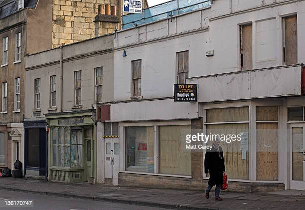 People pass empty and boarded up shops in the centre of Bath on December 28 2011 in Bath England In spite of record postChristmas sale figures many...