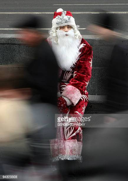 People pass Father Frost as he takes a break during Orthodox Christmas' eve festival in the center of Kiev 06 January 2007 AFP PHOTO/ SERGEI SUPINSKY