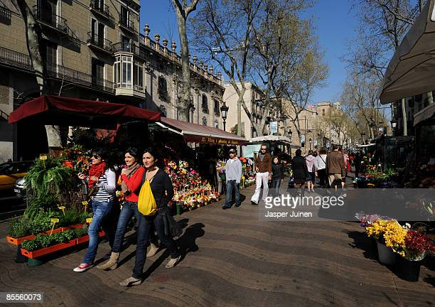 People pass flower market stalls while strolling over Las Ramblas on March 20 2009 in Barcelona Spain