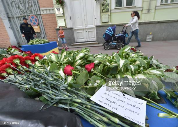 People pass flowers left in front of the British embassy in Kiev on May 23 in tribute to victims of deadly Manchester Arena terror attack Twenty two...