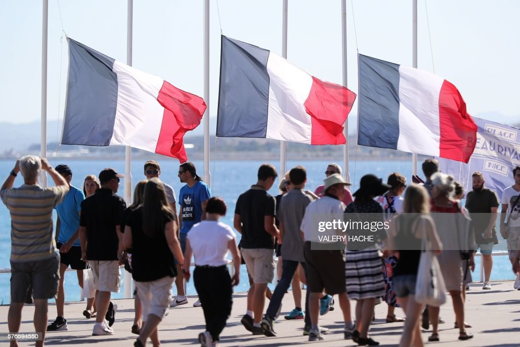 People pass French flags lowered at half-mast in Nice on July 16, 2016, following the deadly Bastille Day attack. The Islamic State group claimed responsibility for the truck attack that killed 84 people in Nice on France's national holiday, a news service affiliated with the jihadists said on July 16. Tunisian Mohamed Lahouaiej-Bouhlel, 31, smashed a 19-tonne truck into a packed crowd of people in the Riviera city celebrating Bastille Day -- France's national day. / AFP / Valery HACHE