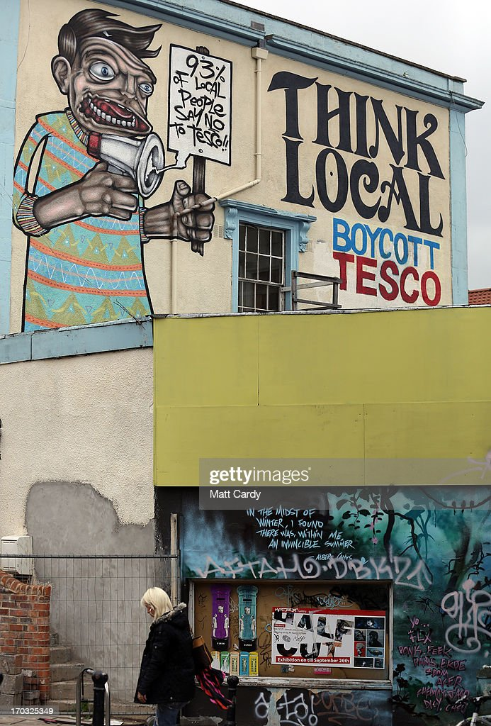 People pass graffiti close to artist Cosmo Sarson's mural of Jesus breakdancing that he has painted on the 8.5 metre wall beside The Canteen in Stokes Croft and is being officially unveiled this evening is reflected in a window, on June 11, 2012 in Bristol, England. The artist was commissioned by The Canteen to paint the wall, which is directly opposite Banksy's Mild Mild West. The controversial 'Breakdancing Jesus', which took 4 days to paint and involved a kilo of glitter and was inspired by an actual event in the Vatican where breakdancers performed to an applauding Pope John Paul II in 2004, is likely to be the latest attraction for graffiti tourists visiting Bristol, often seen the spiritual home of underground artist Banksy.