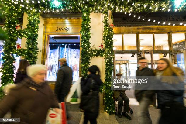 People pass in front of Christmas Show Windows, which are surrounded by illuminations and Christmas decorations at Lord & Taylor New York on Dec. 21 2016.