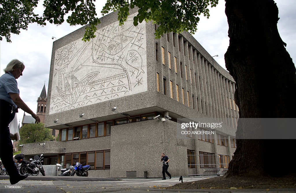 People pass Picasso's mural art work 'The Fisherman' on the government quarter's 'Y building' in Oslo, Norway on August 6, 2013. The art work survived the 22nd July 2011 bombing unscathed, but other government buildings bearing the artist's murals were severely damaged. The Norwegian Directorate for Cultural Heritage fears that Picasso's first monumental concrete murals, which were made between the late 1950s and the early 1970s for two government buildings in Oslo, may be destroyed. The buildings were severely damaged during the deadly terrorist attack in the Norwegian capital in July 2011. The government is now considering whether to demolish the Modernist buildings that form the regjeringskvartal or government quarter. AFP PHOTO / ODD ANDERSEN