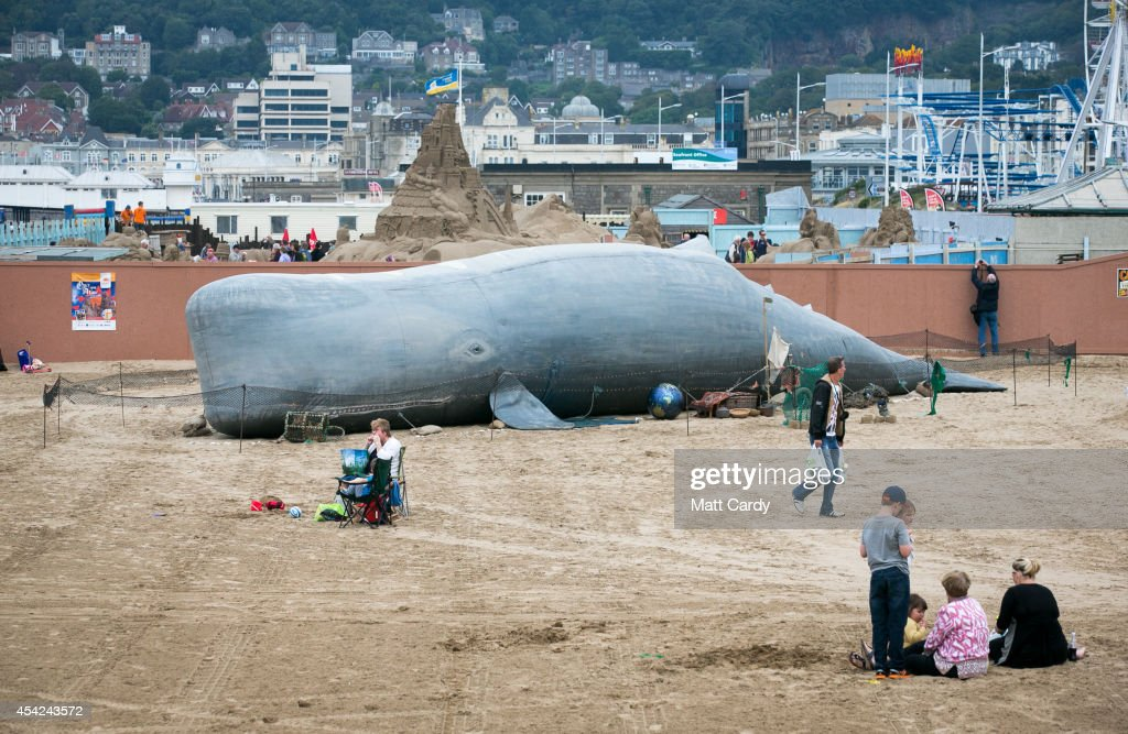 People pass the 50ft (15m) inflatable whale that has been erected on the beach by the Bible Society on August 27, 2014 in Weston-Super-Mare, England. The Bible Society is using the whale to allow the Circo Rum Ba Ba circus troupe to perform the Biblical story of Jonah and the Whale. The whale was brought to Weston after it was banned from London's Hyde Park for being too 'religious'.
