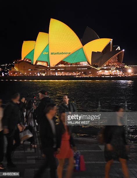 People pass the Sydney Opera House lit up in Australian colours on October 30 to support the Australian Wallabies rugby union team who take on the...