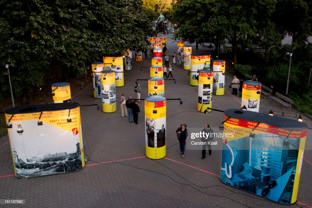 People pass through an installation of yellow pillars depicting the history of Berlin on September 1, 2012 in Berlin, Germany. The installation is part of ongoing exhibitions and events ahead of Berlin's 775th anniversary, which the city will mark with a celebration scheduled for the end of October.