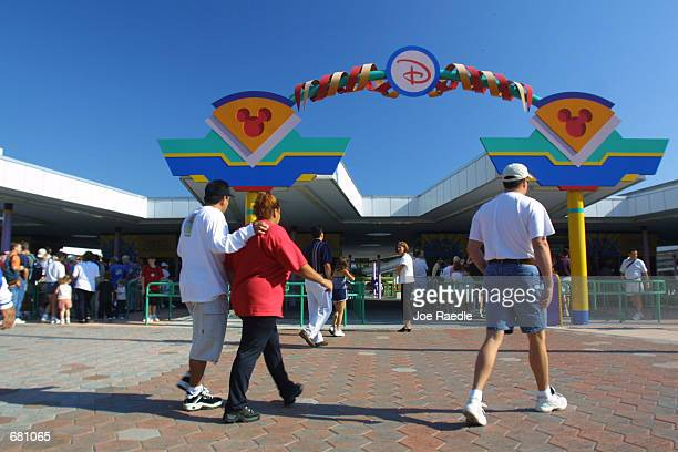 People pass through the ticket/monorail entrance to Walt Disney World November 11 2001 in Orlando Florida