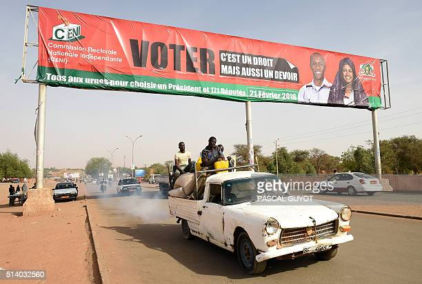 People pass under a billboard of the commission electorale nationale independante which translates as 'To vote is a right but also a duty all to the...