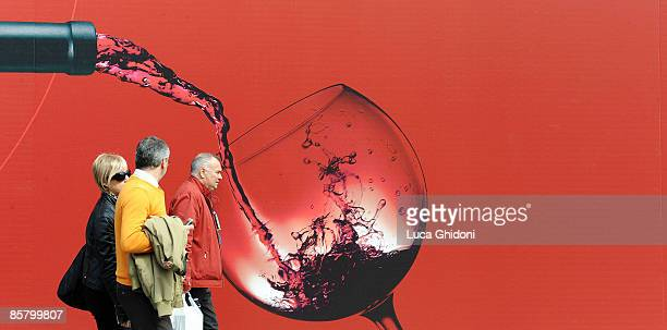 People passe by a giant picture of red wine at the Vinitaly on April 4 2009 in Verona Italy Vinitaly the international wine and spirit exhibition...
