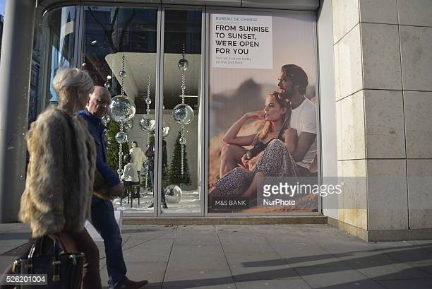 People passing an advert for the Marks and Spencer Bank in Manchester England on Monday 7th December 2015