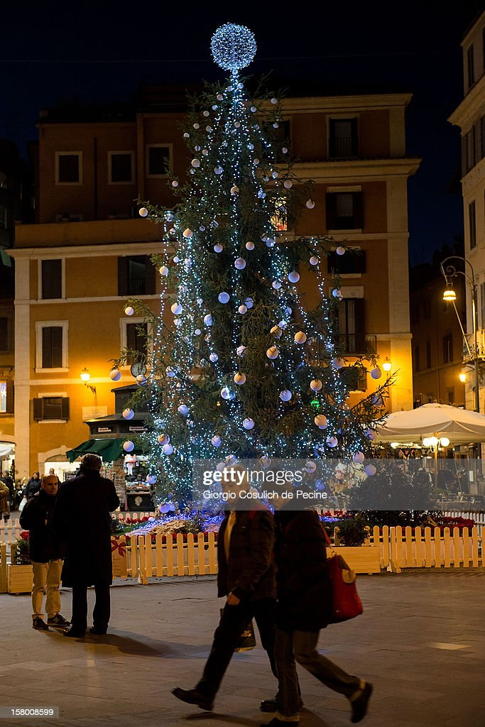 People passing by a Christmas tree, in Piazza San Lorenzo in Lucina, in the downtown area on December 8, 2012 in Rome, Italy.