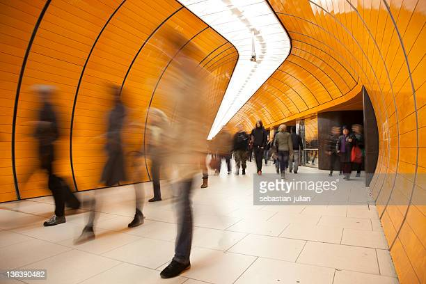 People passing by on modern orange subway