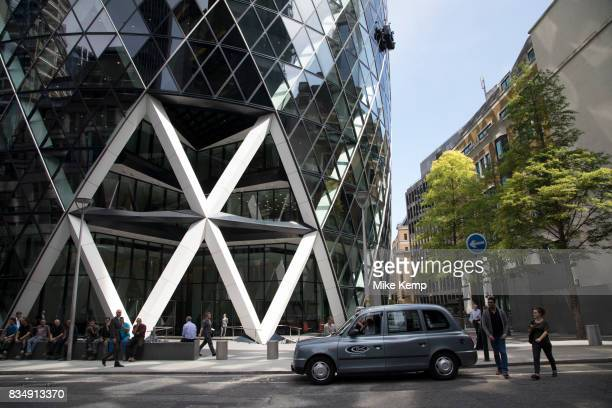 People passing by outside the Gherkin in the City of London England United Kingdom Exterior of the Gherkin at 1 St Mary Axe This iconic building is...