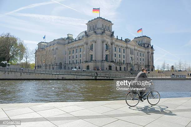 People passing by the Reichstag during a sunny day on April 20 2014 in Berlin Germany The Reichstag home of the Bundestag the German parliament is...