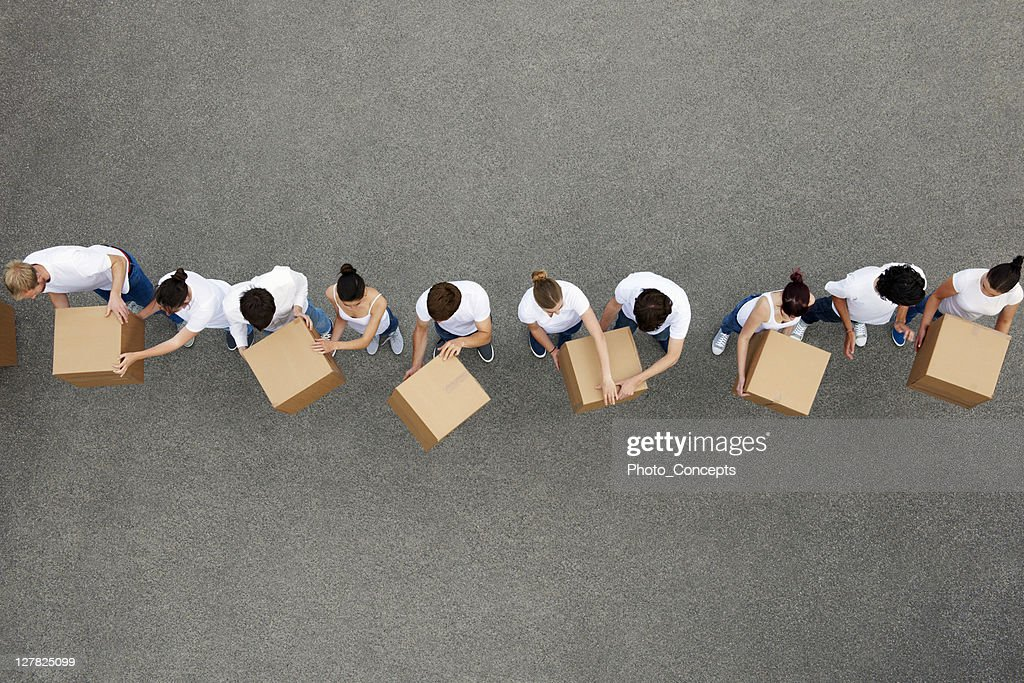 People passing cardboard boxes : Stock Photo