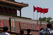 People passing next to a portrait of Chairman Mao and red flags fluttering on the Rostrum in Tiananmen Square Beijing China Tiananmen Square is a...