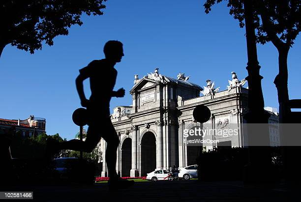 People passing the Puerta de Alcala in the famous Parque Del Retiro on May 20 2010 in Madrid Spain Madrid is a big european city with more than 3...