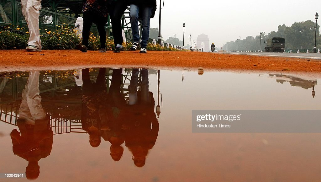 People passing through logged water at Rajpath after the rain on February 4, 2013 in New Delhi, India. MeT Office has predicted that the capital is likely to experience hailstorms and rains in some parts.