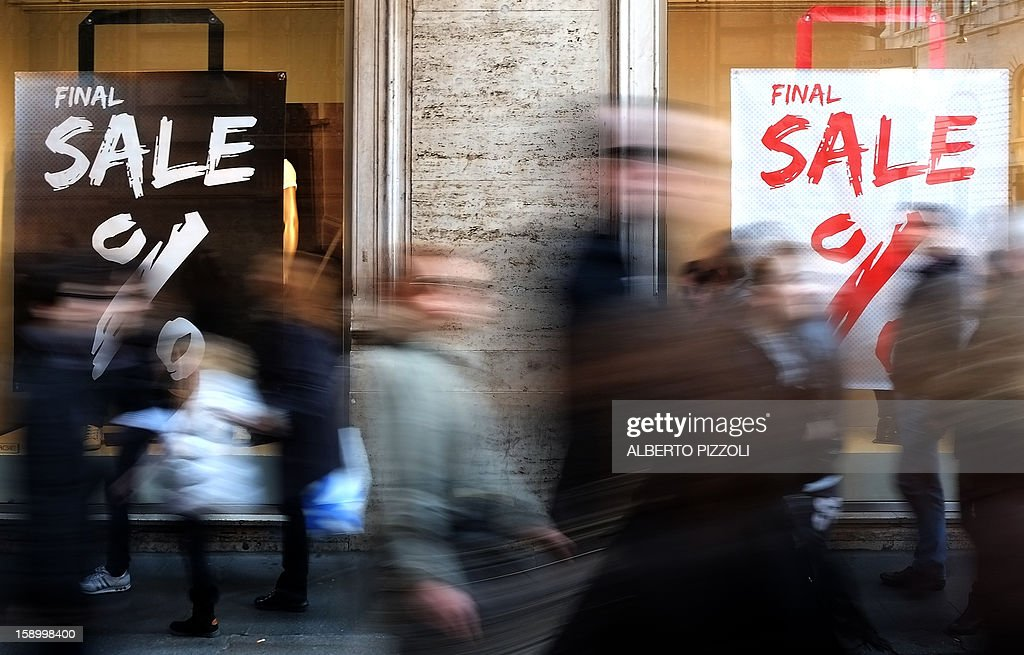 People past a shop advertising its sale, on January 5, 2013 during the first day of sales in Rome.