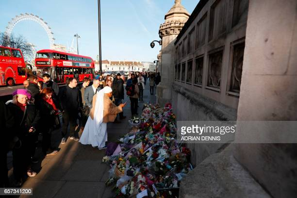 People pause at the floral tributes to the victims of the March 22 terror attack on Westminster Bridge and the British parliament that killed four...
