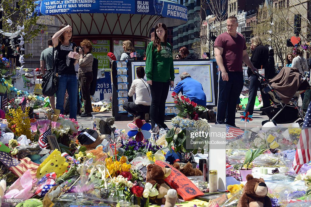 People pause at the memorial site in Copley Square for the deadly attacks on the Boston Marathon on Boylston Street April 30, 2013 in Boston, Massachusetts. Boston continues to return to normalcy with Bolyston Street fully reopened and businesses back up and running following two weeks of closures.