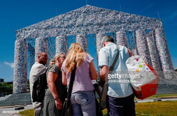 People pause in front of the 'Parthenon of Books' by Argentinian artist Marta Minujin at the Documenta 14 art exhibition in Kassel on June 2 2017 The...