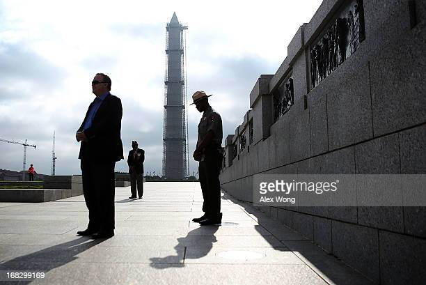 People pause while a prayer is said during a ceremony to celebrate VE Day at the National World War II Memorial May 8 2013 in Washington DC The...
