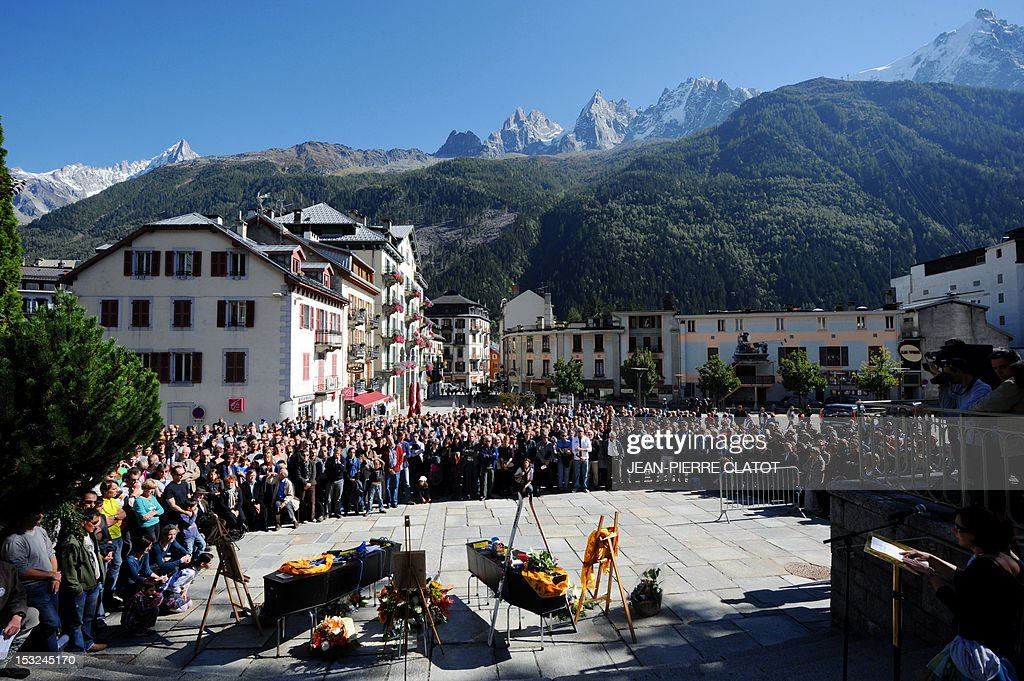 People pay homage in front of the coffins of the French mountain guides Ludovic Challeat and Fabrice Priez, and the portrait of their colleague Remy Lecluse (still missing) during a memorial ceremony to pay tribute to the victims of the last week avalanche on Nepal's Manaslu mountain, on October 2, 2012, in Chamonix, that is considered the birthplace of European alpinism and the home of most of the French climbers killed. The four French -- two guides and two clients -- were among eight people killed after an avalanche swept through their camp on the side of the 8,156-metre (26,759-foot) Himalayan mountain, just hours before the alpinists were to make an attempt to reach the peak's summit. AFP PHOTO / JEAN-PIERRE CLATOT