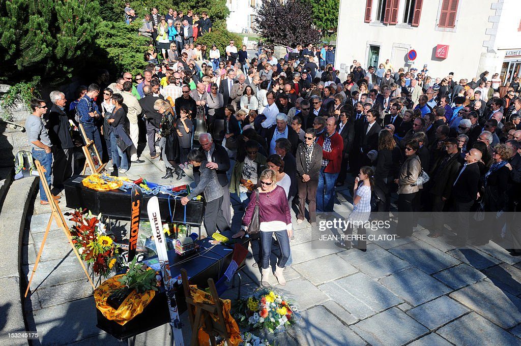 People pay homage in front of the coffins of the French mountain guides Ludovic Challeat and Fabrice Priez, and the portrait of their colleague Remy Lecluse (still missing) during a memorial ceremony to pay tribute to the victims of the last week avalanche on Nepal's Manaslu mountain, on October 2, 2012, in Chamonix, that is considered the birthplace of European alpinism and the home of most of the French climbers killed. The four French -- two guides and two clients -- were among eight people killed after an avalanche swept through their camp on the side of the 8,156-metre (26,759-foot) Himalayan mountain, just hours before the alpinists were to make an attempt to reach the peak's summit.