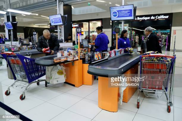 People pay their grocery shopping at the checkout at the exit of an hypermarket store of French retail giant Carrefour in VilleneuvelaGarenne near...