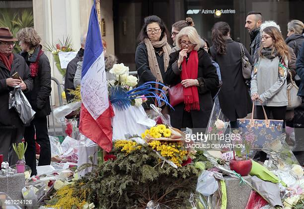 People pay their respect at the entrance of the French weekly newspaper Charlie Hebdo's editorial office on January 9 2015 as a tribute to the 12...